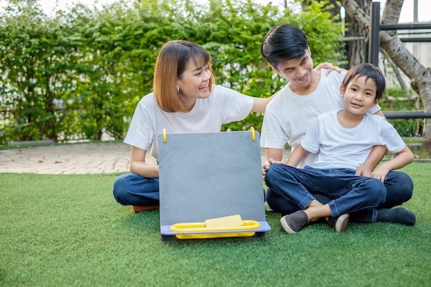 Família asiática pai, mãe e filho brincando com um quadro-negro no jardim da casa