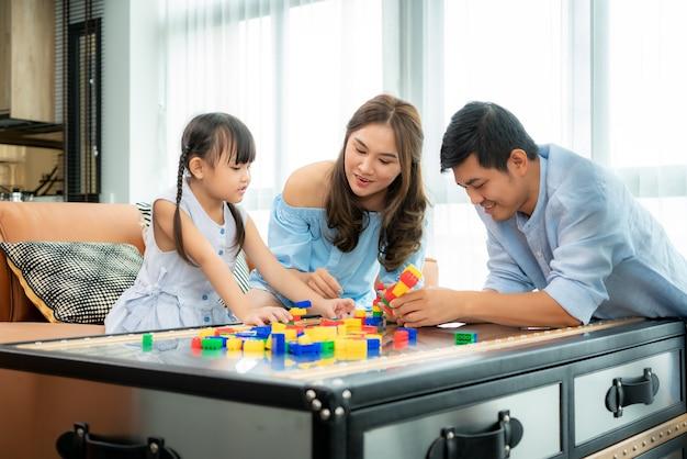 Família asiática passa um tempo na sala de jogos com uma garota brincando
