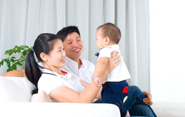 Família asiática que joga com bebê