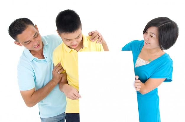 Família asiática que prende a placa branca em branco no fundo branco.