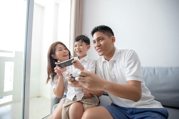 Família asiática se divertindo jogando jogos de console de computador juntos e mãe está aplaudindo o