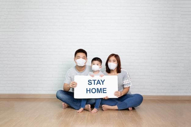Família asiática usando máscara médica protetora para impedir o vírus covid-19 segurando o papel branco com ficar em casa por lado e sentados juntos no chão em casa