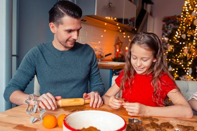 Família assar biscoitos de gengibre no natal