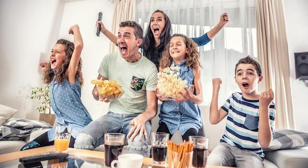 Família assistindo a um jogo de esportes na tv em casa, torcendo e gritando gol com as mãos ao alto, derramando chips e pipoca de emoção.