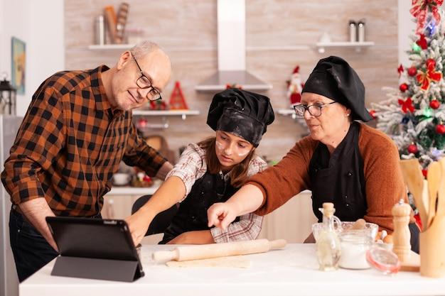 Família assistindo a uma aula de culinária on-line em um tablet em pé à mesa