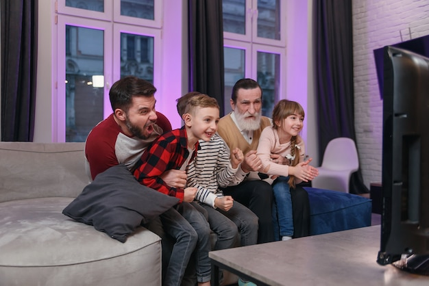 Família assistindo jogo de futebol americano, campeonato no sofá em casa. fãs torcendo emocionalmente pela seleção favorita. filhos com pai e avô desfrutando de lazer em casa.