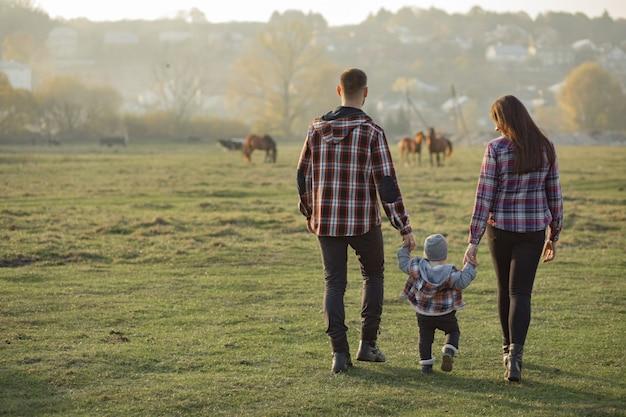 Família bonita andando em um parque por do sol de verão