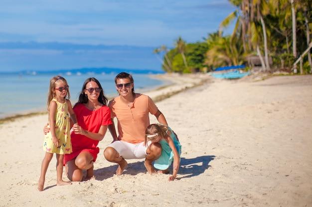 Família bonita de quatro se divertir na praia em filipinas