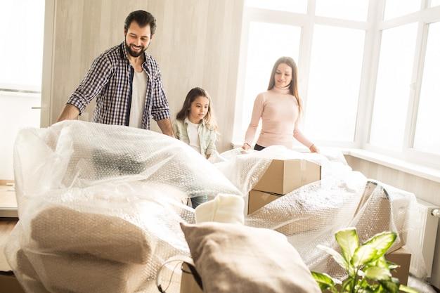 Família bonita e amigável está descompactando suas coisas. eles estão adiando a tampa das caixas. há muitas coisas lá. meninas e homens ficam felizes em se mudar para o apartamento bom e acolhedor.