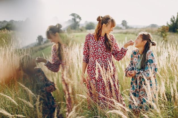 Família bonita e elegante em um campo de verão