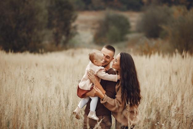 Família bonita e elegante, jogando em um campo