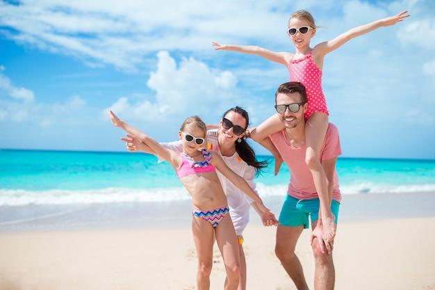 Família bonita feliz de quatro na praia