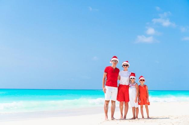 Família bonita feliz em chapéus vermelhos de santa em uma praia tropical que comemora o natal