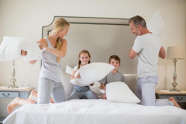Família bonita, tendo uma luta de almofadas no quarto