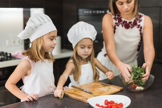 Família bonito na cozinha preparando salada saudável na bancada da cozinha