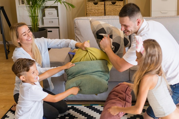 Família brincando com almofadas dentro de casa