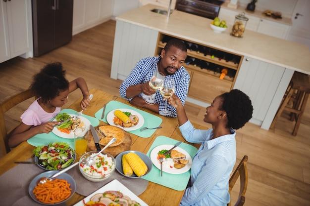 Família brindando com taças de vinho enquanto toma uma refeição na mesa de jantar