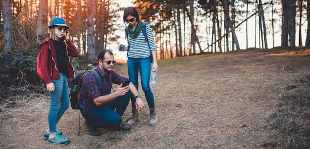 Família, caminhadas na floresta e usando telefone inteligente