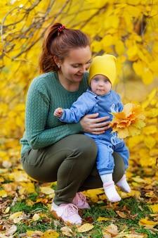 Família caminham mãe e filha no parque de outono.