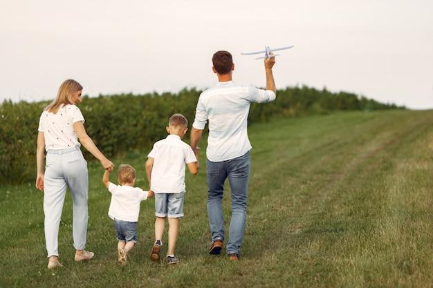 Família caminhando em um campo brincando com um avião de brinquedo