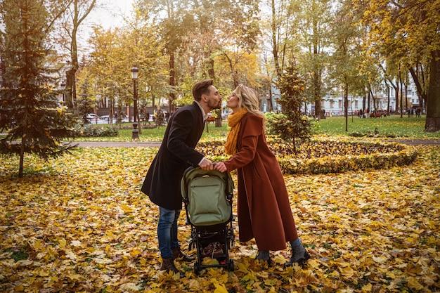 Família caminhando em um parque de outono com um bebê recém-nascido em um carrinho. família ao ar livre em um dourado