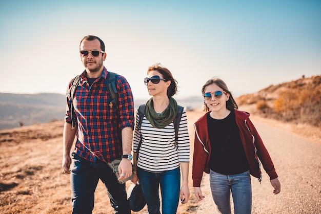 Família caminhando juntos pela estrada de asfalto em um dia ensolarado