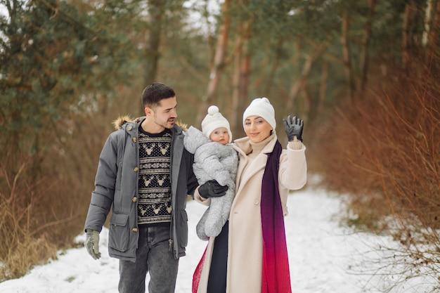 Família caminhando na neve se divertindo no parque de inverno em um dia ensolarado, abraçando-se e sorrindo