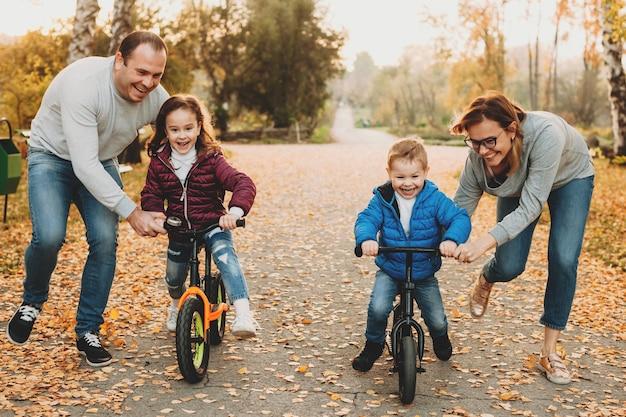 Família caucasiana ajudando os filhos a andar de bicicleta