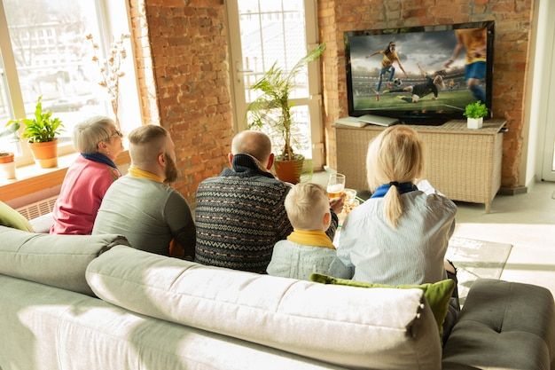 Família caucasiana animada assistindo a um jogo do campeonato de futebol feminino em casa