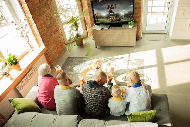 Família caucasiana animada assistindo campeonato de futebol americano, jogo de esporte em casa. avós, pais e filhos torcendo pela seleção nacional favorita. conceito de emoções, apoio, união.