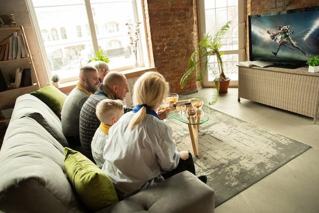 Família caucasiana animada assistindo campeonato de rugby, jogo de esporte em casa. avós, pais e filhos torcendo pela seleção nacional favorita. conceito de emoções humanas, apoio, união.