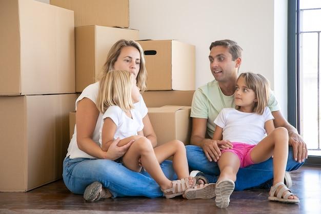 Família caucasiana com crianças cercada de caixas cheias de coisas