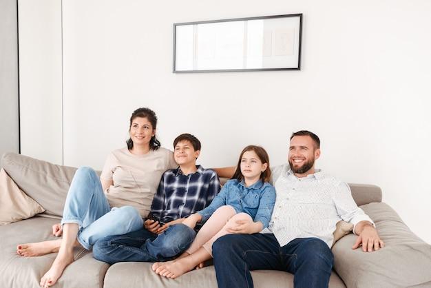 Família caucasiana com dois filhos, descansando na sala de estar de casa e olhando para a tv enquanto estão sentados no sofá