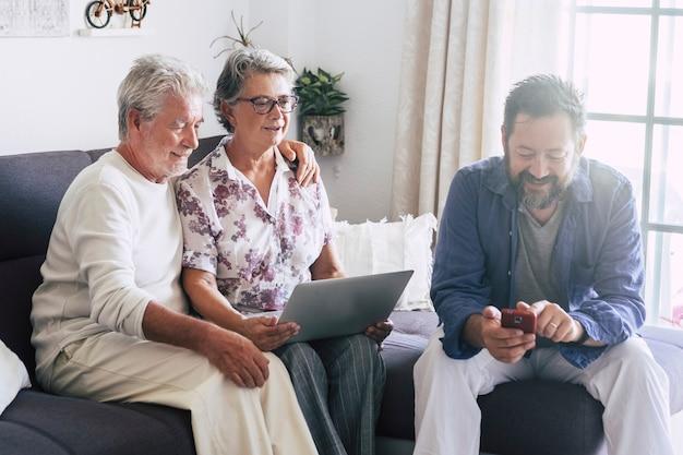 Família caucasiana em casa usando dispositivo de tecnologia moderna como telefone e laptop juntos se divertindo