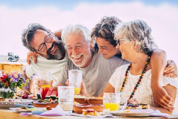 Família caucasiana se abraçando e aproveitando o almoço