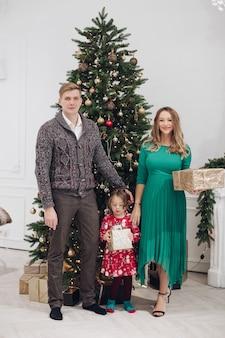 Família caucasiana sorridente ao lado da árvore de natal