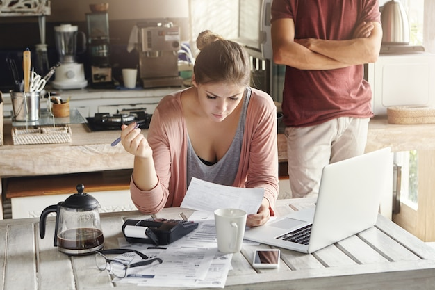 Família caucasiana, tendo dificuldade para pagar as contas. mulher jovem, leitura, documento, com, olhar concentrado, segurando caneta, calculando finanças, em casa