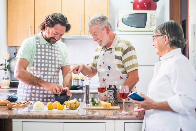 Família caucasiana, três homens cozinham juntos falando sobre o como fazer no celular da mãe