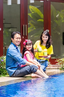 Família chinesa na piscina em frente de casa
