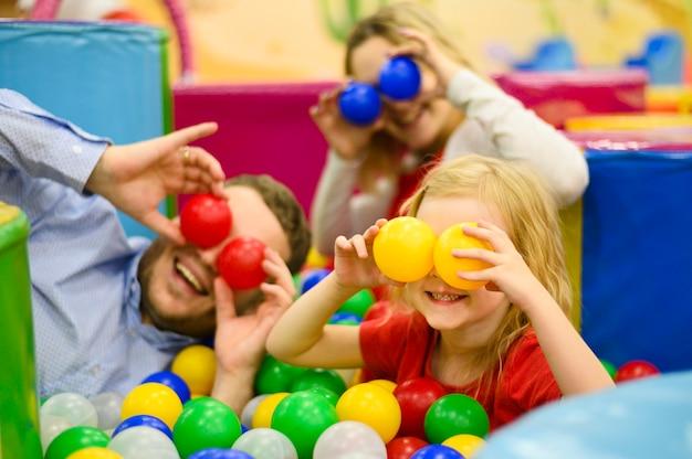 Família cobrindo os olhos com bolas