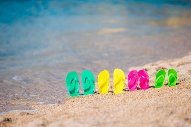 Família colorida flip flops na praia em frente ao mar