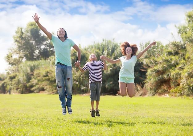 Família com adolescente pulando no parque