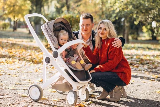 Família com bebê daugher em um carrinho de bebê andando em um parque de outono