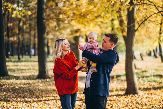 Família com bebê filha caminhando em um parque de outono