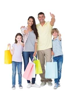 Família com bolsas de compras gesticulando polegares para cima