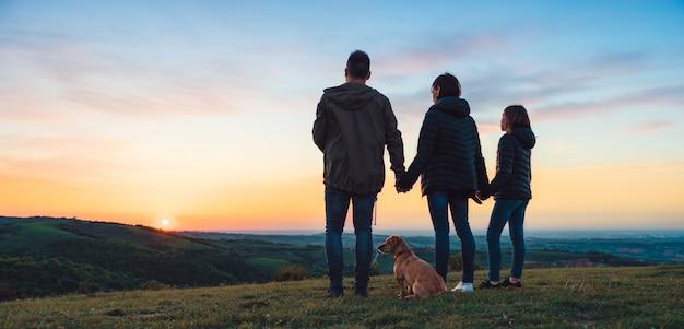 Família com cachorro abraçando em pé na colina