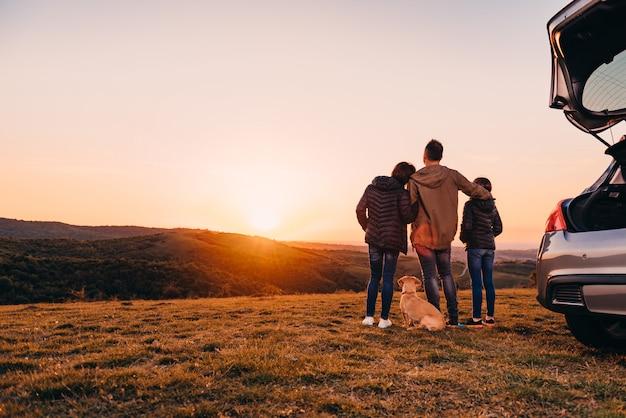 Família com cachorro abraçando na colina e olhando o pôr do sol