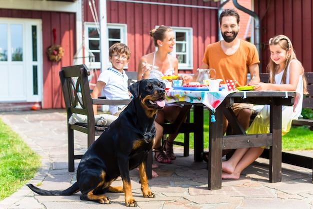 Família com cachorro comendo no jardim em frente à casa