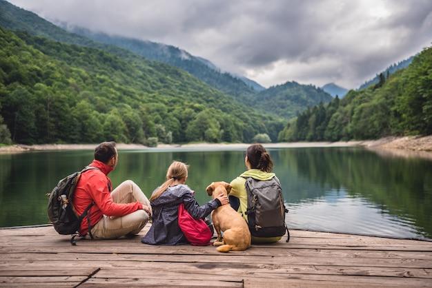 Família com cachorro descansando em um píer