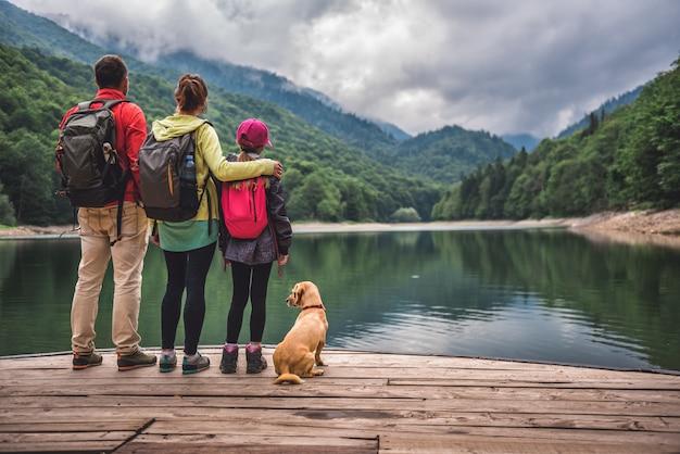 Família com cachorro em pé em um píer